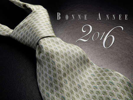bonne: Elegant gray tie on a black background with Bonne annee 2016 as Text