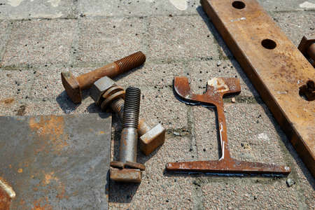 metal fastener: Three big bolts and a key on the ground