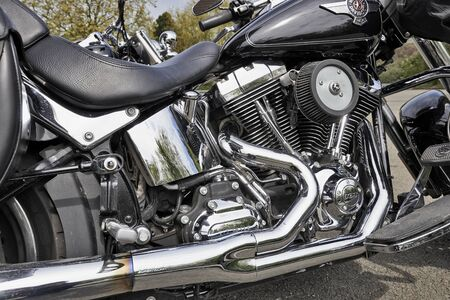 coveted: BRUSSELS, BELGIUM - MAY 01, 2015 Custom Harley Davidson motorcycle engine with  Harley logos. Harley Davidson motorcycles continue to be the most popular and coveted motorcycles for customizing throughout the world.