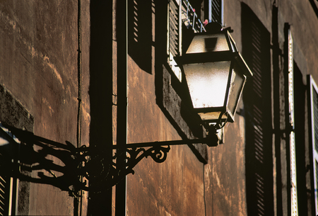 deprived: Brown Roman wall with street lamp and windows at golden hour. Stock Photo