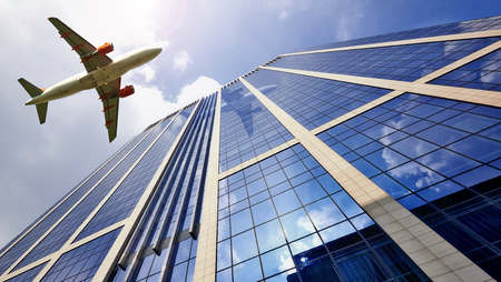 gleaming: A jet plane flying low over Office building with plate glass walls and gleaming steel structure. Stock Photo