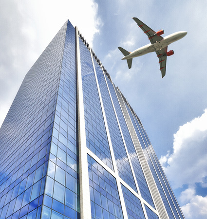 A jet plane flying low over Office building with plate glass walls and gleaming steel structure. Standard-Bild