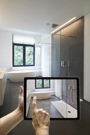Mobile-Gerät mit den Menschen die Hände in gefliestes Bad mit Fenster in Richtung Garten, das Foto
