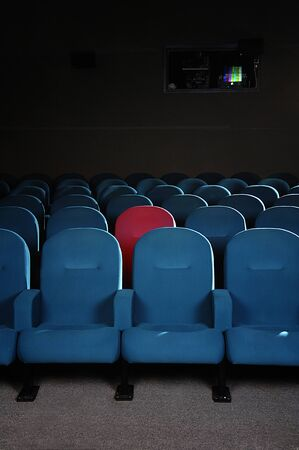 reserved seat: Cinema seats in a movie theater with one reserved seat