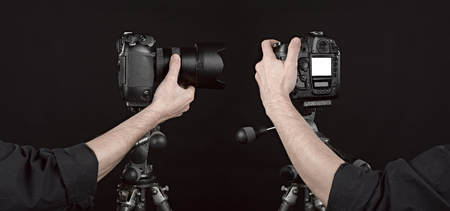 clic: Two angle of Black digital camera on black background with photographer hand pushing the button