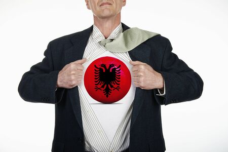 Superhero pulling Open White Shirt with soccer ball flagged Albania on white background Stock Photo