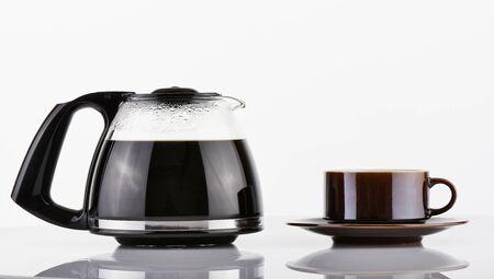 Voll Kaffeekanne und braune Tasse über weißem