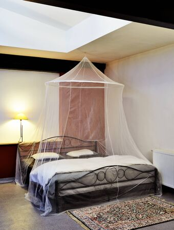restored: Cosi vintage bed with mosquito Net in a restored loft Stock Photo