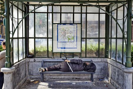 hooded shirt: BRUSSELS, BELGIUM -18 JULY 2015: A homeless sleeping under a dirty tram shelter in Brussels, Belgium on 18 July 2015