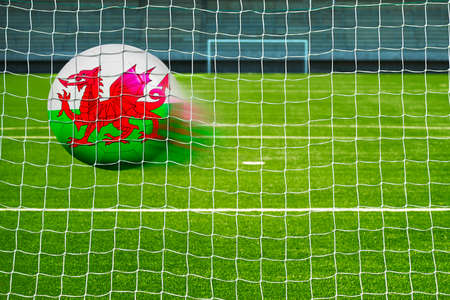 goal flag: Shot on goal, soccer ball with the flag of Wales in the net Stock Photo