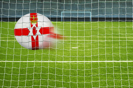 penalty flag: Shot on goal, soccer ball with the flag of North Ireland in the net Stock Photo