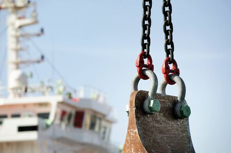 dredging: Two chains, bolt and nut Supported a pestle for dredging harbor, blurred industrial boat in background Stock Photo