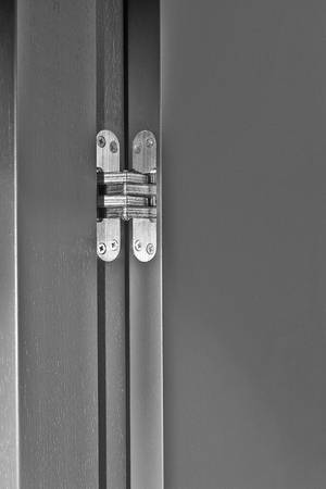 Silver hinge attached to black wooden door Фото со стока
