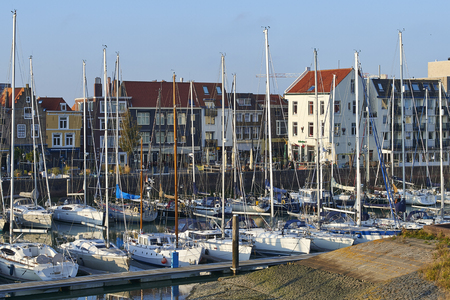 VLISSINGEN, NETHERLANDS, OCTOBER 22, 2016; Old harbor of the Dutch town of Vlissingen or Flushing, with sailing boats and old houses on the quay under a beautiful blue sky Editorial