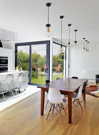 Empty table and chairs in luxury living room with view on garden