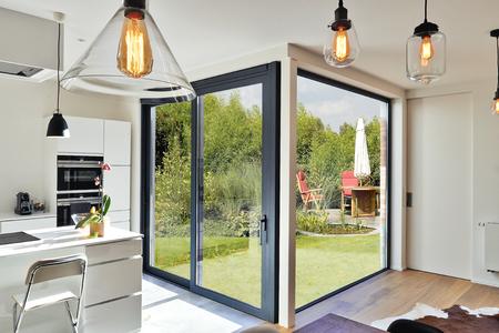 スライドドアと緑豊かなガーデン ビューのモダンなラグジュアリ キッチン改修
