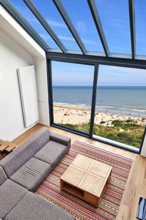 Modernes Wohnzimmer mit großen Fenstern und Blick auf Meer Lizenzfreie Bilder