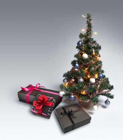 Mini Christmas Tree on gradient background with copy space and some gift box Stock Photo