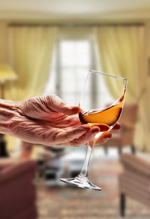 Pink wine swirled in glass in luxury living room Stock Photo