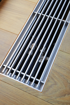 Heating grid with ventilation by the floor in hardwood flooring Stock Photo