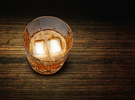 Perfecto vaso de whisky y hielo en el fondo de madera con textura