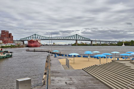 MONTREAL, QUEBEC, CANADA - 19 MAY 2017: View of Old Montreals beach, buildings, St. Lawrence River and Jacques Cartier bridge Editorial
