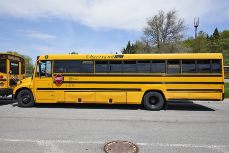 molson: MONTREAL, QUEBEC, CANADA - 18 MAY 2017: School bus waiting for children in a parking at the Mont Royal in Montreal