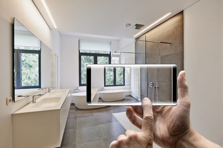 정원쪽으로 windows와 함께 타일 된 욕실에서 사진을 찍는 사람 손으로 모바일 장치 스톡 콘텐츠