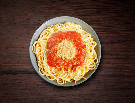 Dish of spaghetti bolognese on wooden texture
