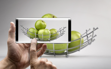 Two hands holding a mobile Smartphone and take a picture of a Modern fruit basket with green apples Lizenzfreie Bilder