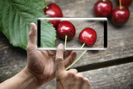 Two hands holding a mobile Smartphone and take a picture of the cherries on a wooden table