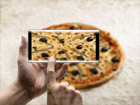 Two hands holding a mobile Smartphone and take a picture of a delicious pizza