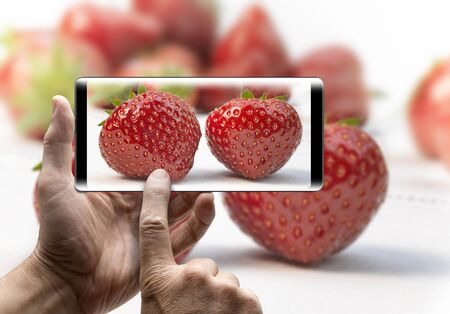 Two hands holding a mobile Smartphone and take a picture of fresh strawberries