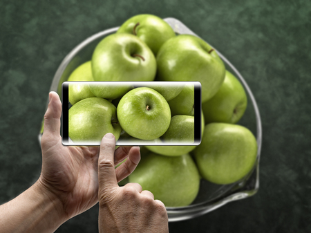Two hands holding a mobile Smartphone and take a picture of  green apples Lizenzfreie Bilder