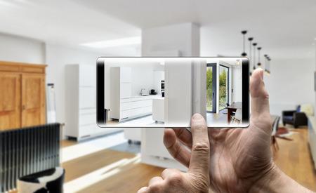携帯電話スマート フォンとモダンで豪華なリビング ルームとキッチンの写真を保持している 2 つの手 写真素材