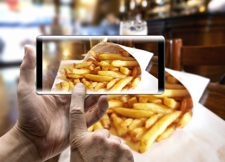 Two hands holding a mobile Smartphone and take a picture of Potatoes fries in a little white paper bag Lizenzfreie Bilder