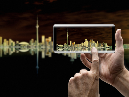 Two hands holding a mobile Smartphone and take a picture of Beautiful Toronto Cityscape with Water Reflection