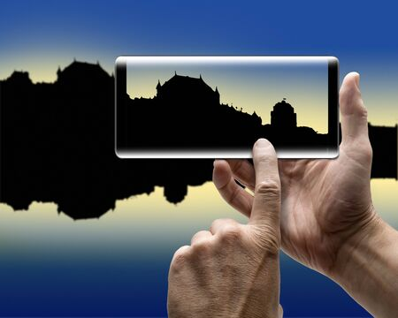 Two hands holding a mobile Smartphone and take a picture of a city silhouette