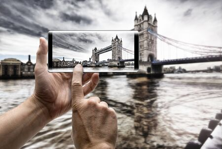 Two hands holding a mobile Smartphone and take a picture of Tower Bridge on Thames river in London Lizenzfreie Bilder
