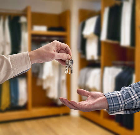 Man is handing a house key to a other man in modern dressing room