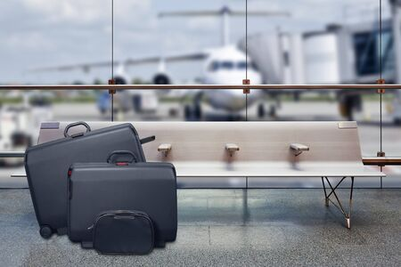 Suitcases in the airport departure lounge, airplane in the blurred background, summer vacation concept, traveler suitcases in airport terminal waiting area