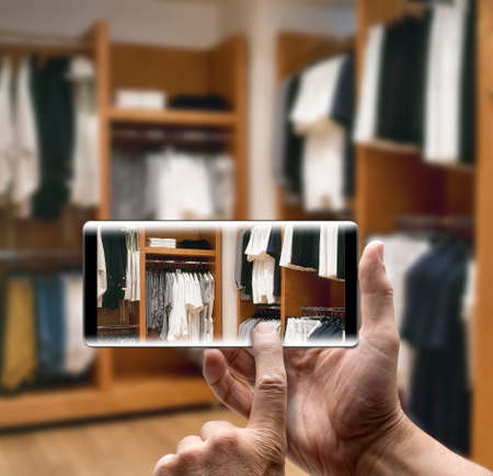 Two hands holding a mobile Smartphone and take a picture of a modern dressing room