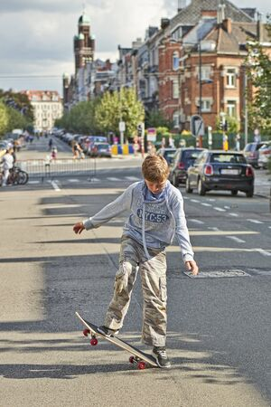 BRUSSELS, BELGIUM - SEPTEMBER 17, 2017: Young teenager boy practice skateboarding during the Car Free Streets day on Demolder Ave. in Brussels, Belgium