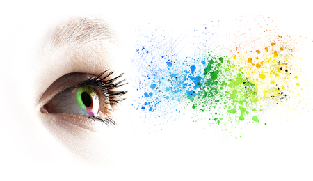 Occhio femminile dell'arcobaleno variopinto e spruzzatura colorata sopra bianco