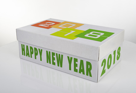 White shoe box with 2018 Happy New Year words on white table with reflection Standard-Bild