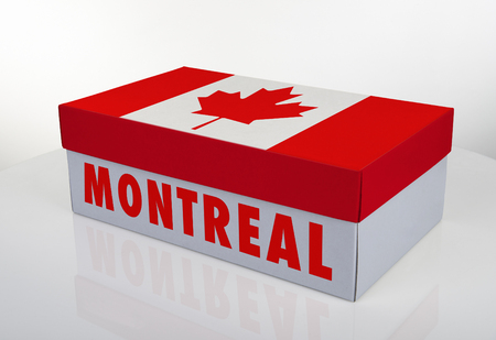 White shoe box and Canadian flag on white table with reflection