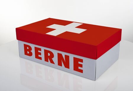 White shoe box and Swiss flag on white table with reflection, Clipping Path for the box