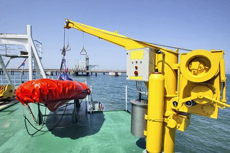 Lifeboat from the side of a ship and his crane Stok Fotoğraf