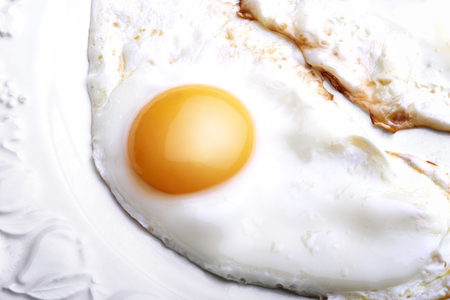 One egg baked and dressed on white plate in close-up