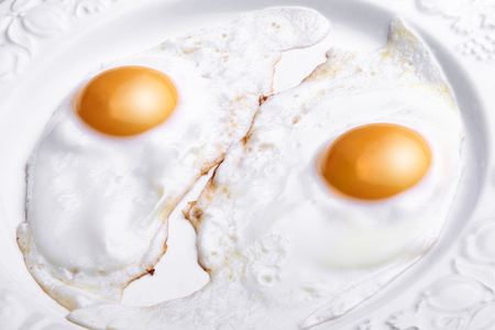 Two eggs baked and dressed isolated on white plate in close-up